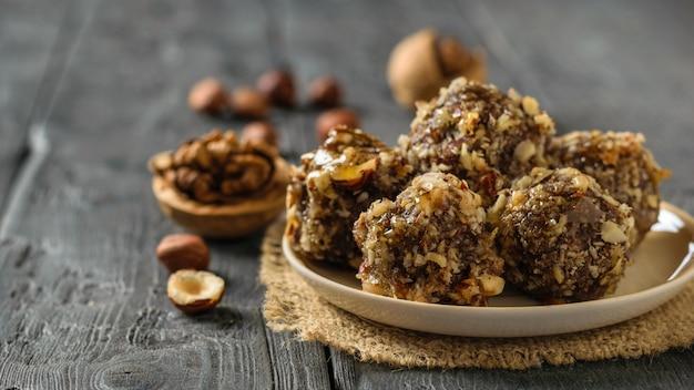 Walnüsse und kugeln aus nüssen, getrockneten früchten und schokolade auf einem schwarzen tisch. leckere frische hausgemachte süßigkeiten.