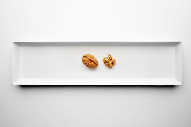 Walnuss geschlossen und geöffnet isoliert in der mitte der rechteckigen keramikplatte auf weißem tisch