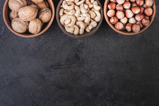 Walnuss, haselnuss und cashewnüsse in keramik, ansicht von oben