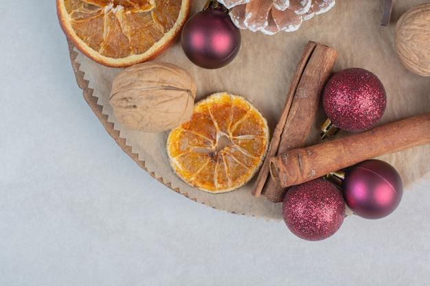 Walnuss mit tannenzapfen und weihnachtskugeln auf holzteller. hochwertiges foto