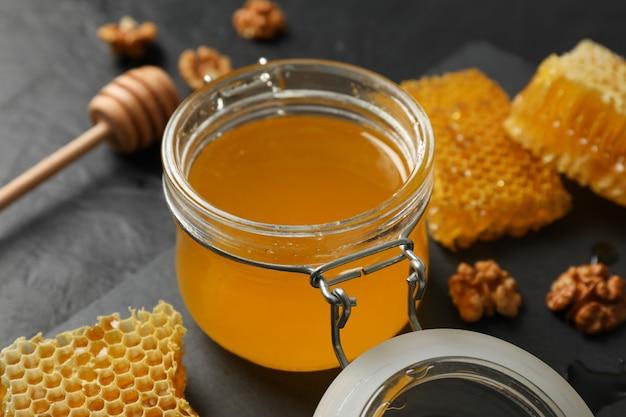Walnuss, waben, glas mit honig und schöpflöffel auf schwarz