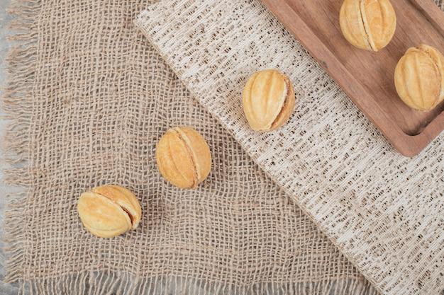 Walnussförmige kekse auf sackleinen und teller.