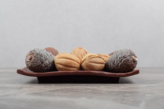 Walnussförmige kekse und tannenzapfen auf dunklem teller.