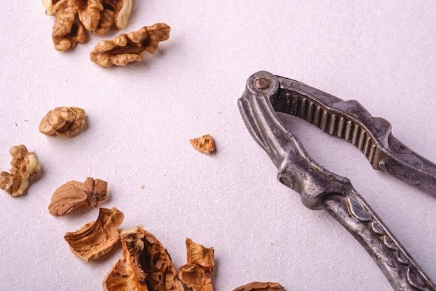 Walnusshaufenfutter mit halb geschälter nuss, rissige nussschale, nahe weinlese-nussknacker auf weißem hintergrund, winkelansicht, gesundes nahrungsmittelkonzept