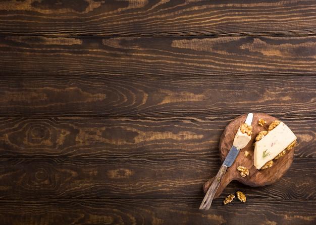 Walnusskäse mit käse und speziellem messer auf altem hölzernem rundem brett.