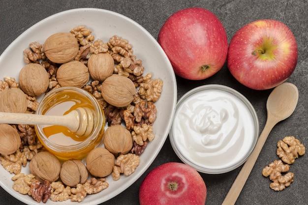 Walnusskerne und ganze walnüsse, glas mit honig in weißer keramikschale, joghurt und rote äpfel auf dem tisch. schwarzer hintergrund. flach legen