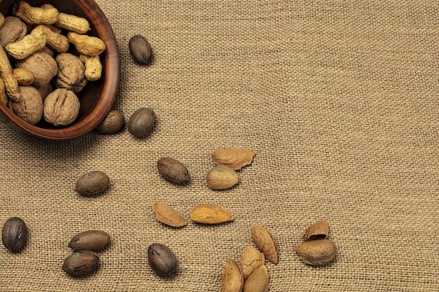 Walnussmandeln-erdnüsse in einer hölzernen schüssel über hölzernem hintergrund.