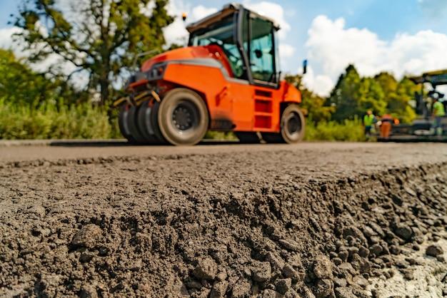 Walze bei asphaltarbeiten, walze beim straßenbau bei asphaltarbeiten