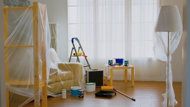 Walzenbürste auf leiter bei wohnungsrenovierung. plastikfolie. zuhause während der renovierung, dekoration und malerei. instandhaltung von innenwohnungen. rolle, leiter für die hausreparatur