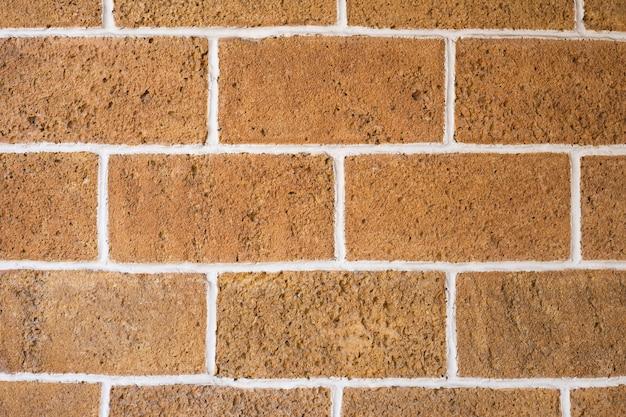 Wand aus orangefarbenem stein mit weißen nähten, textur. orange backsteinmauer hintergrund