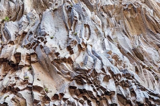 Wand aus vulkanischer lava des ätna. die textur des steins ist dunkelgrau gefärbt. natürlicher hintergrund.