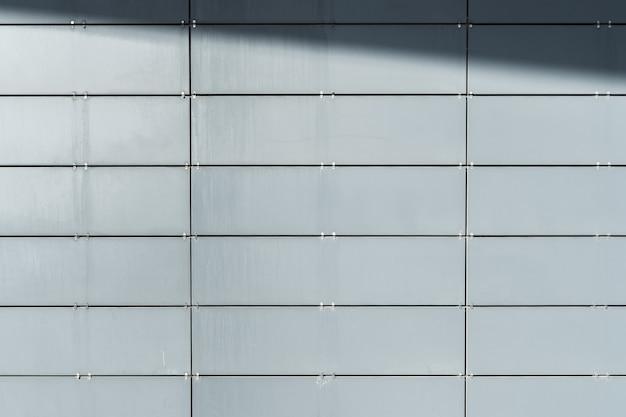 Wand des modernen gebäudes mit verkleidungsplatten mit schatten beschichtet. abstrakter architektonischer hintergrund