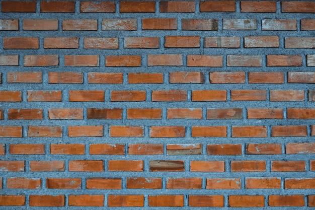 Wand-fragmenthintergrund des roten backsteins oder backsteinschichtgebäudebeschaffenheit.