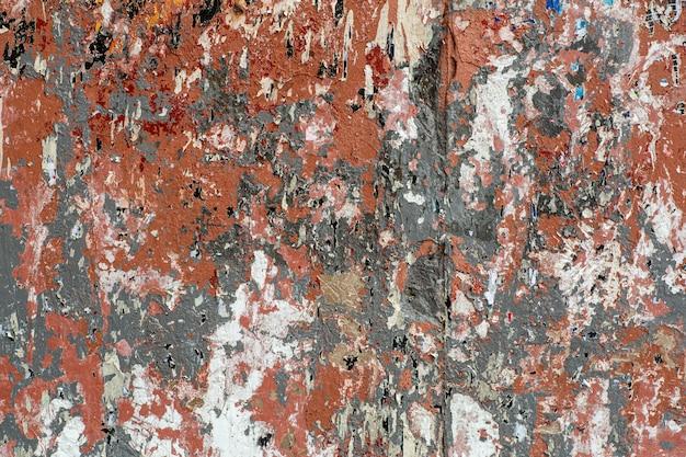 Wand mit spuren von alter abblätternder farbe, zerrissenem papier und leimhintergrund.