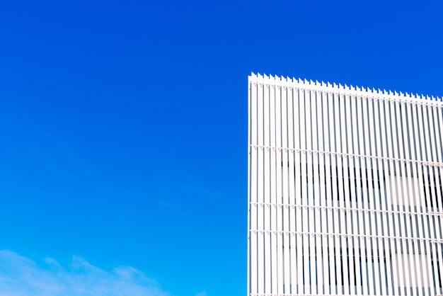 Wand mit weißmetallbrettern und blauem himmel