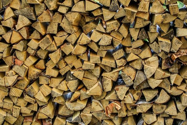 Wandbrennholz, hintergrund von trocken gehackten brennholzstämmen in einem stapel
