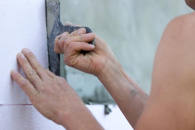 Wanddämmung mit styroporplatten, klebstoffauftrag und installation.