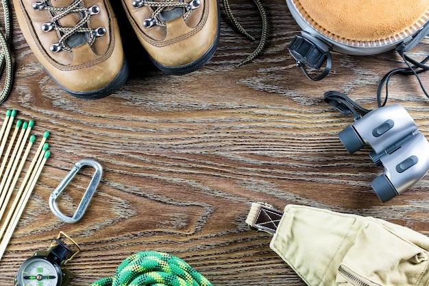 Wander- oder reiseausrüstung mit stiefeln, kompass, fernglas, streichhölzern auf holzhintergrund. aktives lifestyle-konzept
