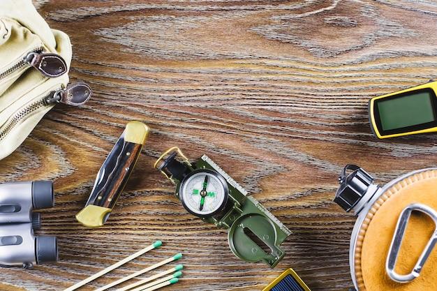 Wander- oder reiseausrüstung mit stiefeln, kompass, fernglas, streichhölzern auf holzhintergrund. aktives lifestyle-konzept.