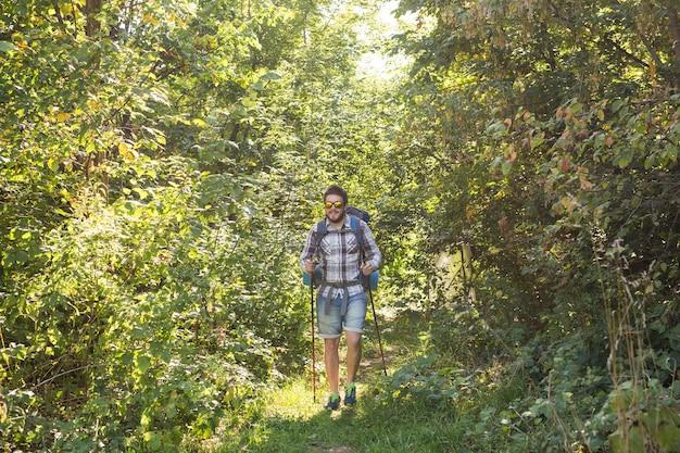 Wander-, tourismus- und naturkonzept - junger reisender mit rucksack über wald stehend