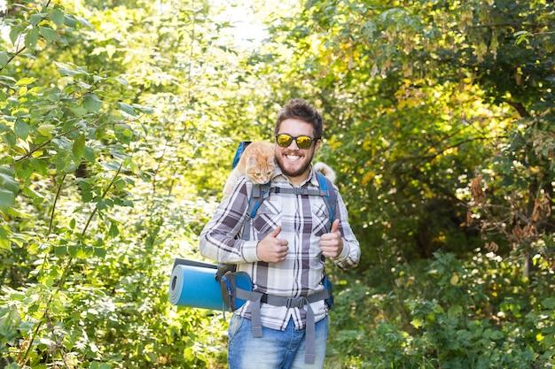 Wander-, tourismus- und naturkonzept - junger reisender mit rucksack und überstehender katze