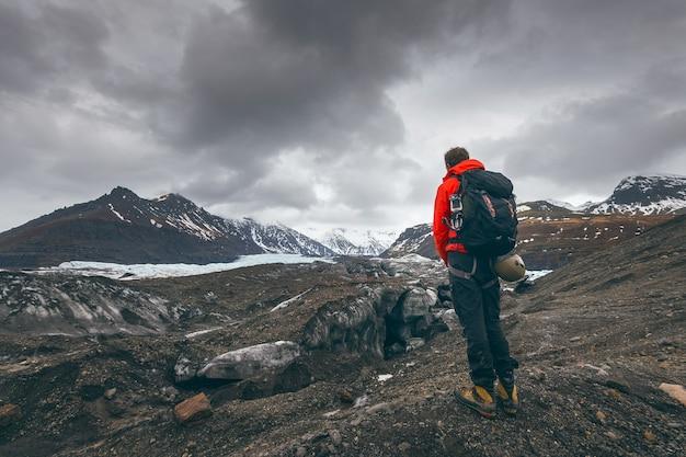 Wanderabenteuerreisemann, der gletscher in island beobachtet.