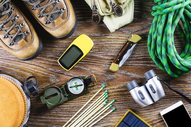 Wanderausrüstung mit stiefeln, kompass, fernglas, streichhölzern, reisetasche auf holzhintergrund. aktives lifestyle-konzept.
