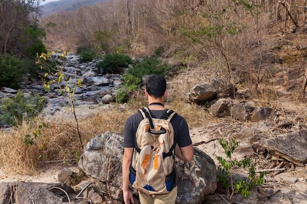 Wanderer am blick auf den fluss von hinten