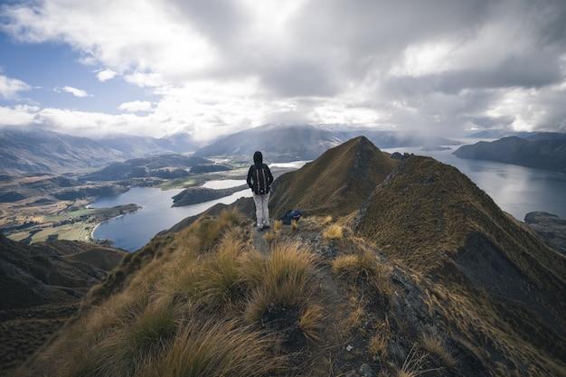 Wanderer an der spitze eines berges an einem bewölkten tag
