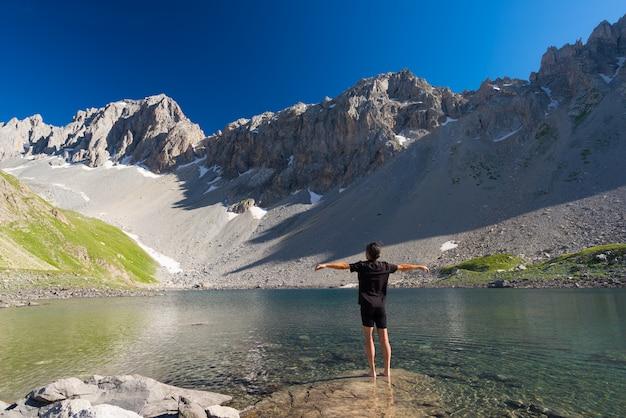 Wanderer, der am blauen see der großen höhe in der idyllischen unberührten umwelt sich entspannt sommerabenteuer auf den alpen.