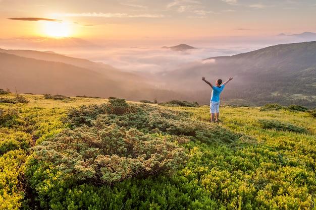 Wanderer, der auf einen berg mit den angehobenen händen steht und sonnenaufgang genießt