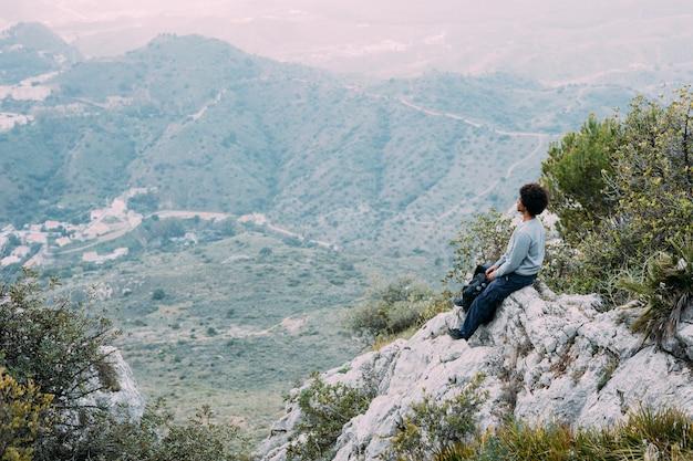 Wanderer, der auf felsen sitzt