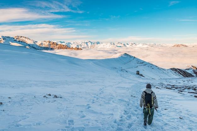 Wanderer, der auf schnee auf den alpen wandert.