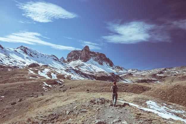 Wanderer, der die hervorragende ansicht der landschaft der großen höhe und der majestätischen schneebedeckten bergspitze in der herbstsaison schaut.