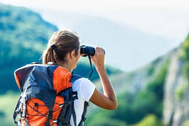 Wanderer, der im fernglas schaut und einen spektakulären blick auf die bergspitze über den wolken genießt