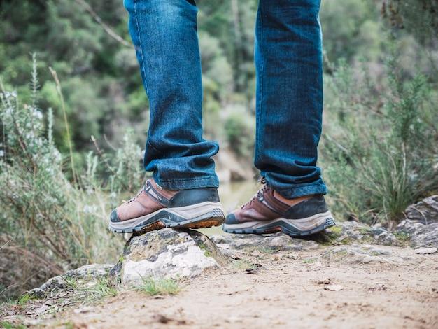 Wanderer, der über felsen auf einem bergweg wandert