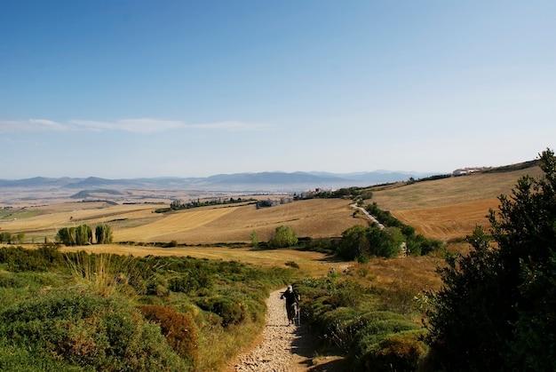 Wanderer gehen einen felsigen weg in richtung der heiligen stadt santiago, spanien.