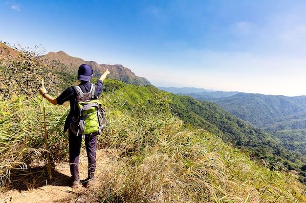 Wanderer hebt die arme und zeigt auf die spitze eines berges