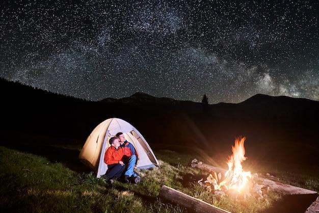 Wanderer in der nähe von lagerfeuer und touristenzelt in der nacht