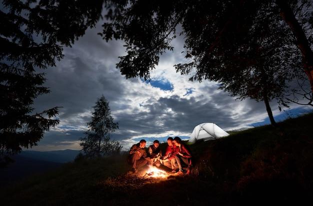 Wanderer in der nähe von lagerfeuer und zelt bei nacht camping