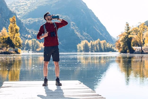 Wanderer junger mann reisender mit rucksack trinkwasser beim stehen vor dem see.