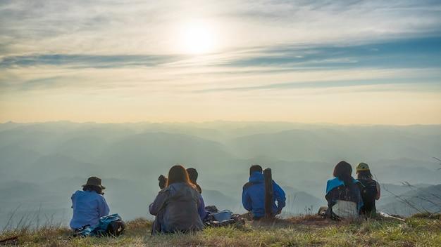 Wanderer leute machen eine pause und sitzen auf berggipfel