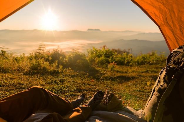 Wanderer-mann, der in einem touristischen zelt durch reise-entdeckungs-konzept sitzt