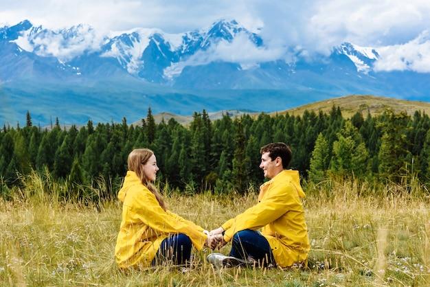 Wanderer mann und frau sitzen händchen haltend vor dem hintergrund der alpen auf ihrer urlaubsreise.