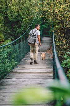 Wanderer mit dem hund, der über hölzerne hängebrücke geht