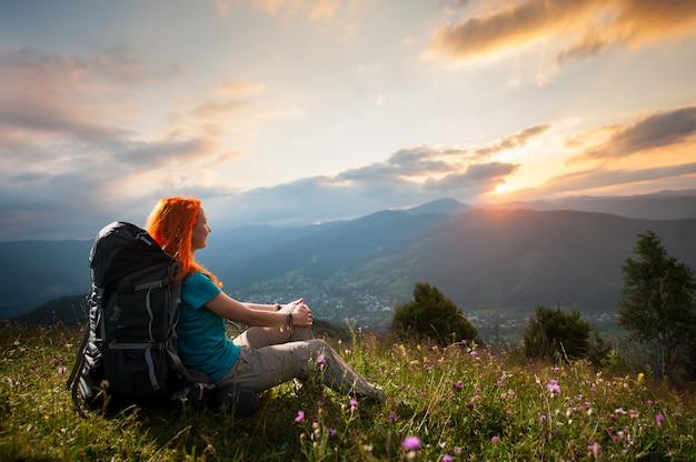 Wanderer mit einem rucksack bei sonnenuntergang