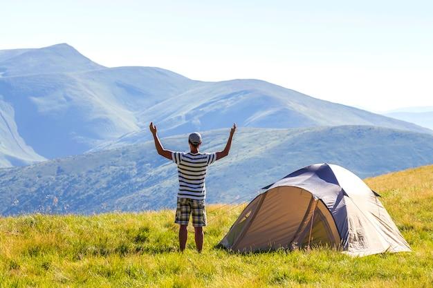 Wanderer mit erhobenen händen in bergen.
