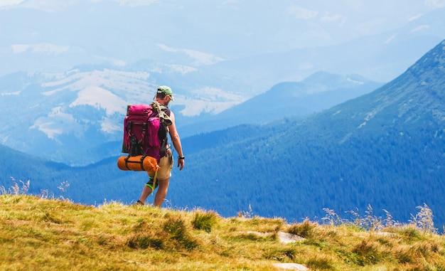 Wanderer mit großem rucksack auf blauen bergen