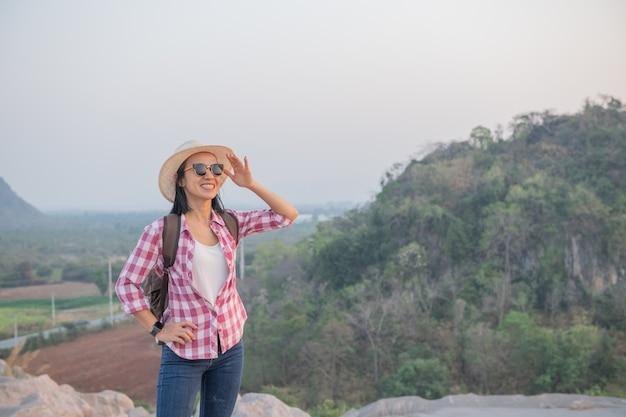 Wanderer mit rucksack, der auf einem berg steht und einen atemberaubenden talblick genießt