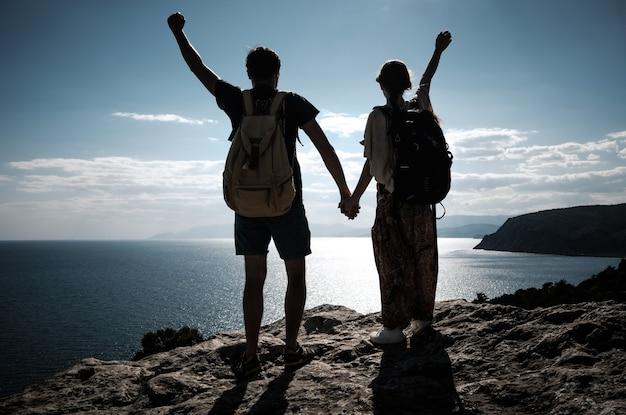 Wanderer mit rucksack stehen auf einem berg mit erhobenen händen und genießen die aussicht. teamarbeit, mann und frau